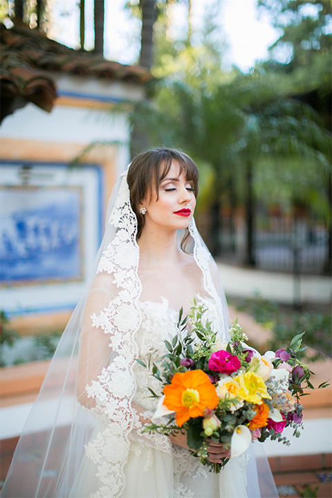 Rancho las lomas spanish inspired wedding shoot bride form fitting strapless lace gown with sweetheart neckline and long veil with lace trim and crystal belt holding bright floral bridal bouquet