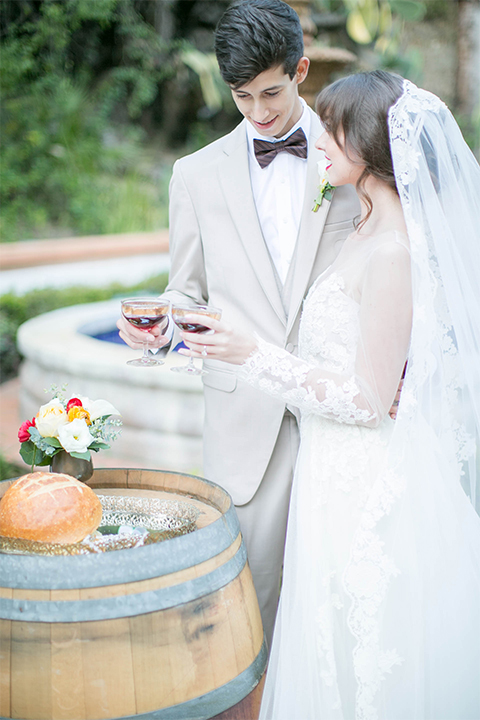 Rancho las lomas spanish inspired wedding shoot bride form fitting strapless lace gown with sweetheart neckline and long veil with lace trim and crystal belt with groom tan suit with matching vest and white dress shirt with dark grey bow tie holding glasses during ceremony