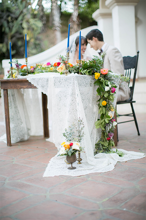 Rancho las lomas spanish inspired wedding shoot bride form fitting strapless lace gown with sweetheart neckline and long veil with lace trim and crystal belt with groom tan suit with matching vest and white dress shirt with dark grey bow tie sitting at table