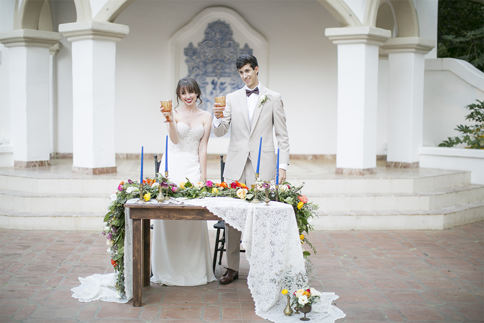 Rancho las lomas spanish inspired wedding shoot bride form fitting strapless lace gown with sweetheart neckline and long veil with lace trim and crystal belt with groom tan suit with matching vest and white dress shirt with dark grey bow tie standing by table