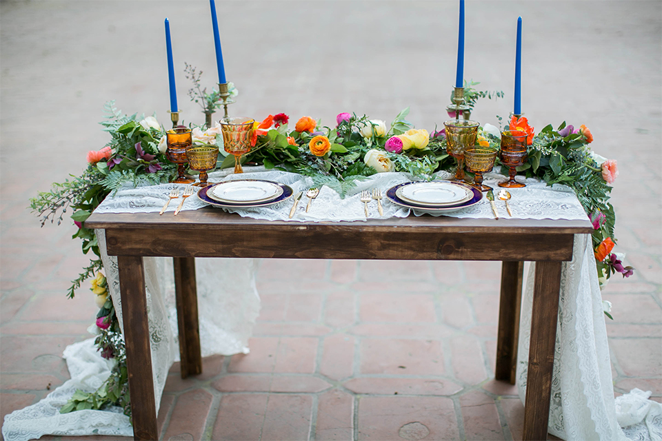 Rancho las lomas spanish inspired wedding shoot table set up with dark brown wood table and white lace table runner with green pink and orange flower centerpiece decor with tall blue candles and chairs