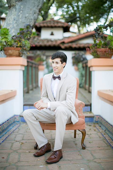 Rancho las lomas spanish inspired wedding shoot groom tan suit with matching vest and white dress shirt with dark grey bow tie sitting on chair