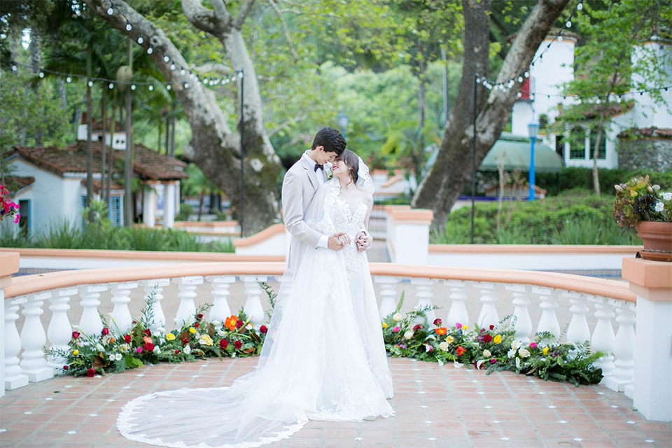 Rancho las lomas spanish inspired wedding shoot bride form fitting strapless lace gown with sweetheart neckline and long veil with lace trim and crystal belt with groom tan suit with matching vest and white dress shirt with dark grey bow tie hugging