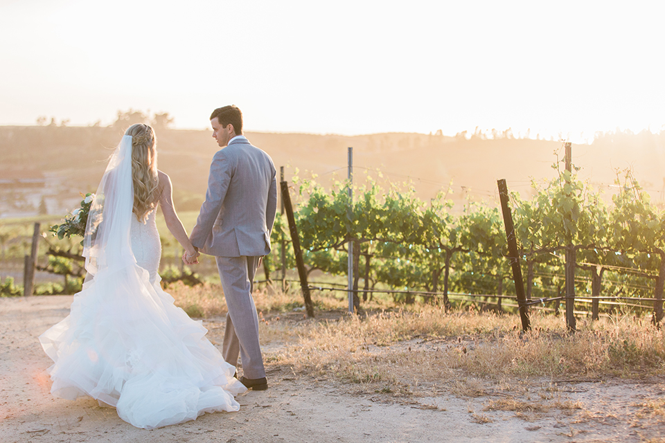 Temecula outdoor wedding at falkner winery bride mermaid style gown with lace bodice and sweetheart neckline with ruffled skirt and long veil with groom heather grey suit with white dress shirt and long white tie with matching pocket square and white floral boutonniere walking and holding hands