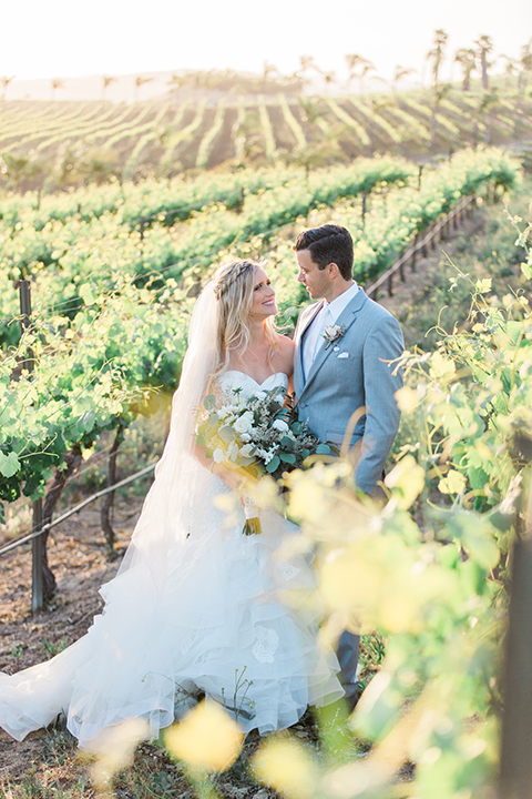 Temecula outdoor wedding at falkner winery bride mermaid style gown with lace bodice and sweetheart neckline with ruffled skirt and long veil with groom heather grey suit with white dress shirt and long white tie with matching pocket square and white floral boutonniere hugging in vineyard bride holding white and green floral bridal bouquet