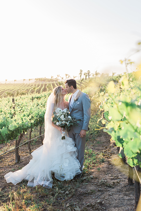 Temecula outdoor wedding at falkner winery bride mermaid style gown with lace bodice and sweetheart neckline with ruffled skirt and long veil with groom heather grey suit with white dress shirt and long white tie with matching pocket square and white floral boutonniere kissing in vineyard bride holding white and green floral bridal bouquet