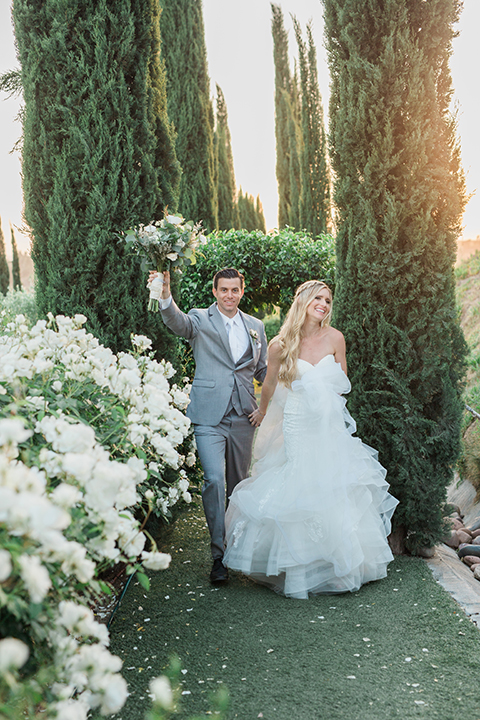 Temecula outdoor wedding at falkner winery bride mermaid style gown with lace bodice and sweetheart neckline with ruffled skirt and long veil with groom heather grey suit with white dress shirt and long white tie with matching pocket square and white floral boutonniere walking and holding hands groom holding brides white and green floral bridal bouquet