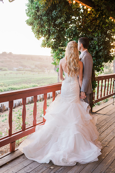 Temecula outdoor wedding at falkner winery bride mermaid style gown with lace bodice and sweetheart neckline with ruffled skirt and long veil with groom heather grey suit with white dress shirt and long white tie with matching pocket square and white floral boutonniere holding hands on balcony