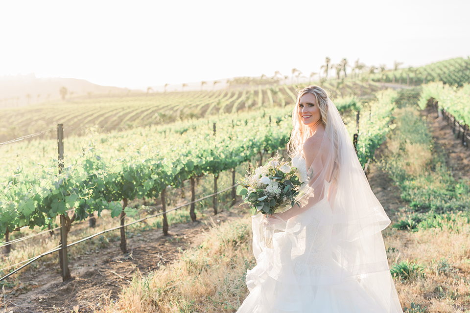 Temecula outdoor wedding at falkner winery bride mermaid style gown with lace bodice and sweetheart neckline with ruffled skirt and long veil holding white and green floral bridal bouquet in vineyard