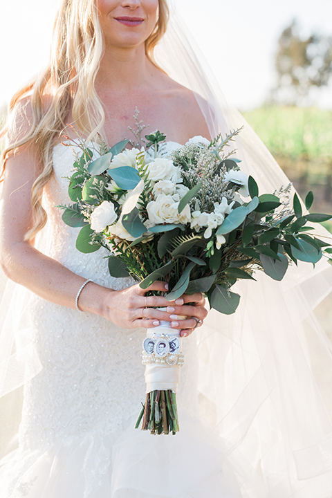 Temecula outdoor wedding at falkner winery bride mermaid style gown with lace bodice and sweetheart neckline with ruffled skirt and long veil holding white and green floral bridal bouquet in vineyard close up
