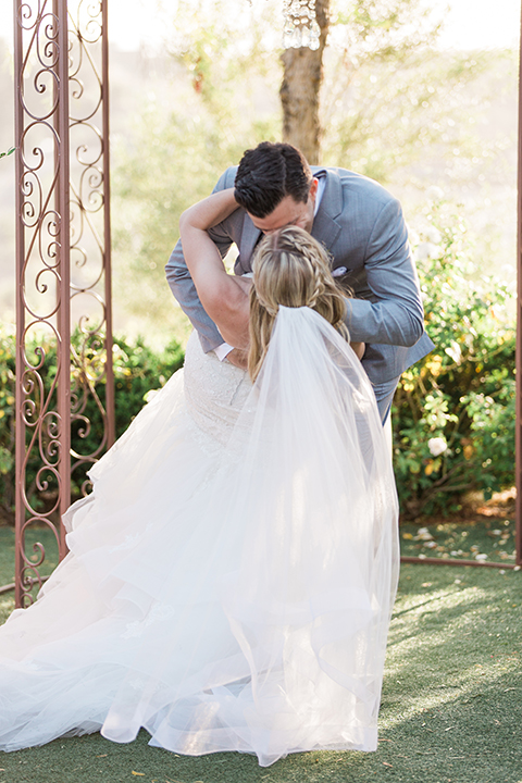 Temecula outdoor wedding at falkner winery bride mermaid style gown with lace bodice and sweetheart neckline with ruffled skirt and long veil with groom heather grey suit with white dress shirt and long white tie with matching pocket square and white floral boutonniere kissing during ceremony