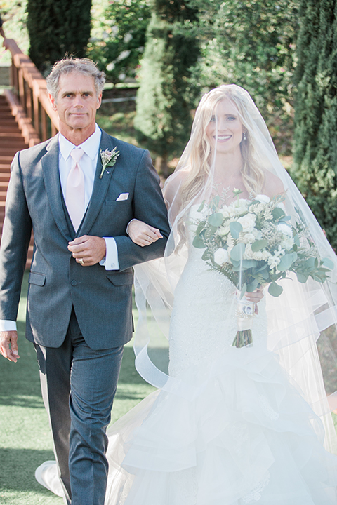 Temecula outdoor wedding at falkner winery bride mermaid style gown with lace bodice and sweetheart neckline with ruffled skirt and long veil holding white and green floral bridal bouquet in vineyard walking down the aisle with dad veil over head