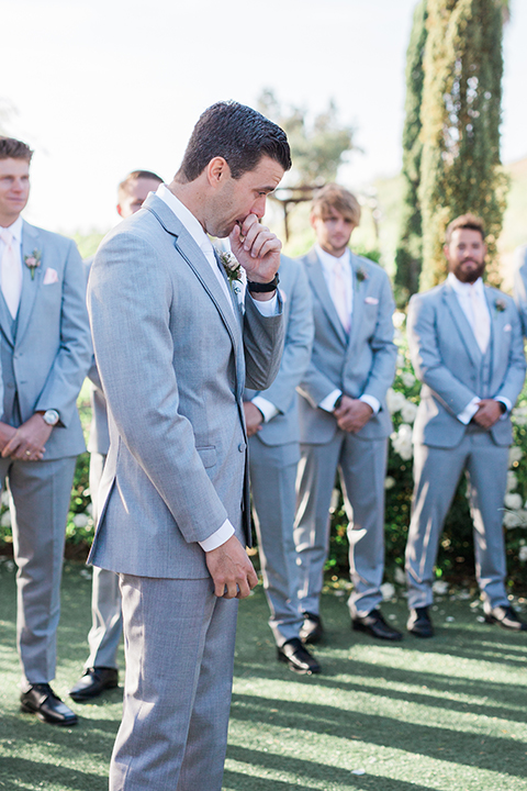Temecula outdoor wedding at falkner winery groom heather grey suit with matching vest and white dress shirt with long white tie and matching pocket square with white floral boutonniere crying watching bride walk down the aisle