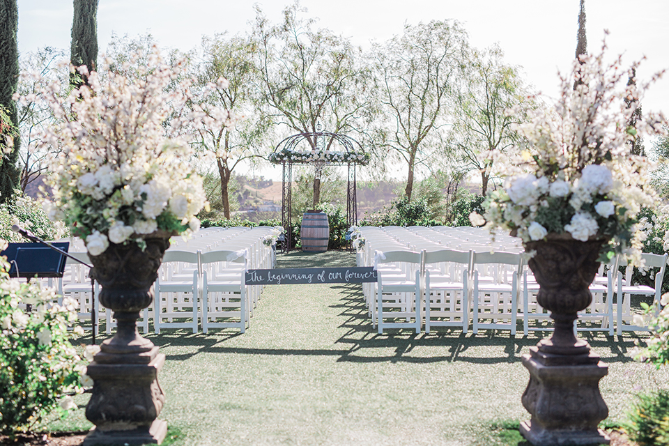 Temecula outdoor wedding at falkner winery ceremony set up on grass with white chairs and altar with flower decor and trees in background with sign at entrance wedding photo idea for ceremony
