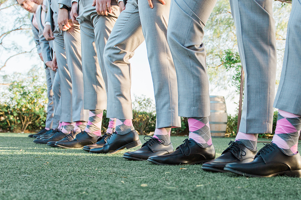 Temecula outdoor wedding at falkner winery groom heather grey suit with matching vest and white dress shirt with long white tie and matching pocket square with white floral boutonniere with groomsmen heather grey suits with long white ties and pink and grey plaid socks with black shoes