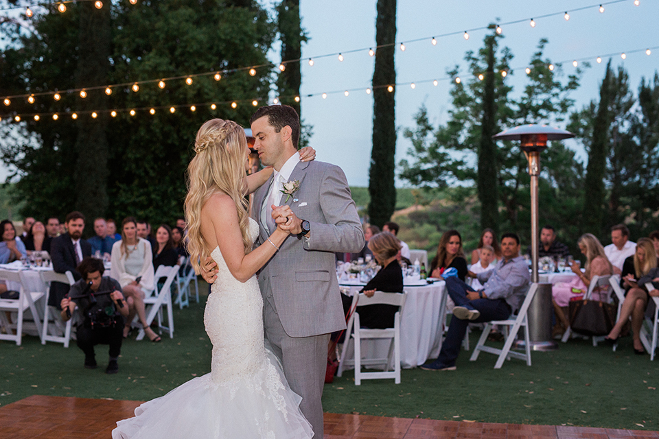Temecula outdoor wedding at falkner winery bride mermaid style gown with lace bodice and sweetheart neckline with ruffled skirt and long veil with groom heather grey suit with white dress shirt and long white tie with matching pocket square and white floral boutonniere first dance