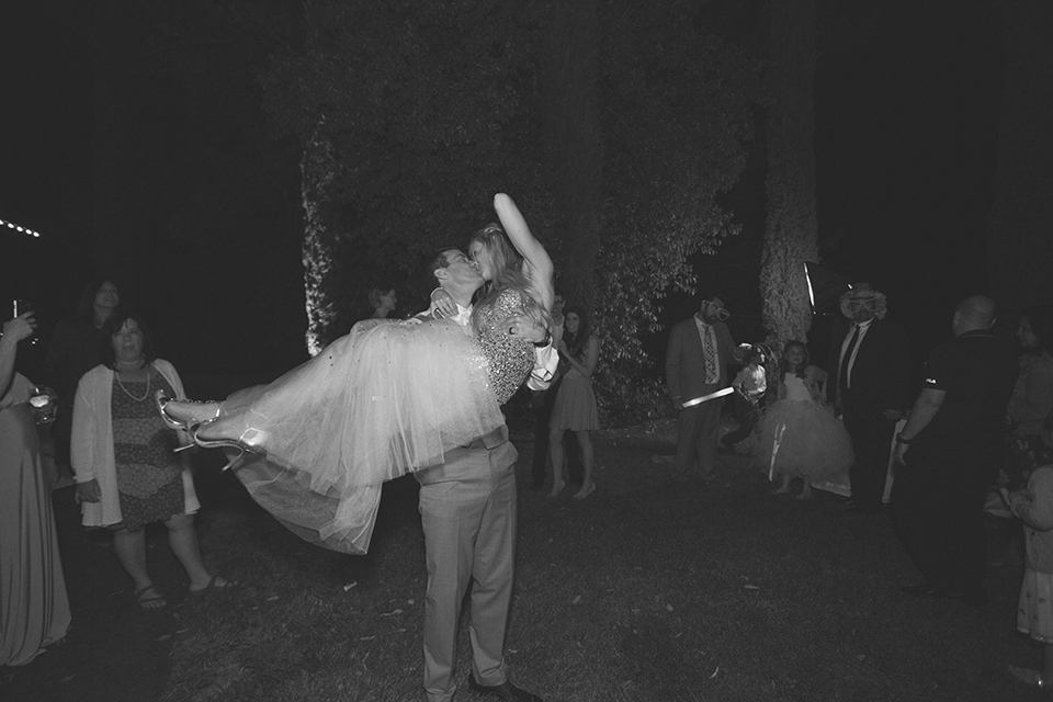 Temecula outdoor wedding at falkner winery bride mermaid style gown with lace bodice and sweetheart neckline with ruffled skirt and long veil with groom heather grey suit with white dress shirt and long white tie with matching pocket square and white floral boutonniere kissing at reception black and white photo