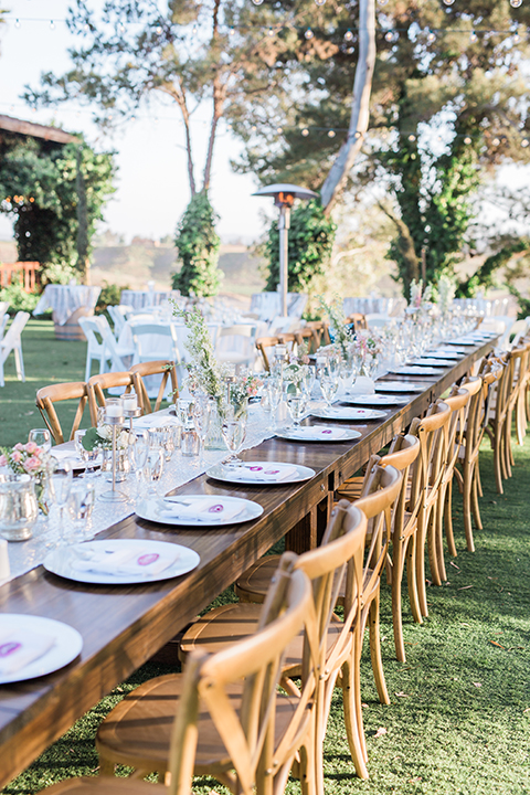 Temecula outdoor wedding at falkner winery reception set up with tables white table linen with white chairs and white place settings with pink and white name place and white flower decor with long light brown wood table with matching wood chairs and flower decor
