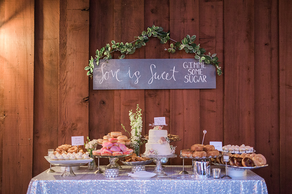 Temecula outdoor wedding at falkner winery reception set up with dessert table white linen with three tier white wedding cake on stand and assortment of donuts and treats with hanging sign and flower decor wedding photo idea for desserts