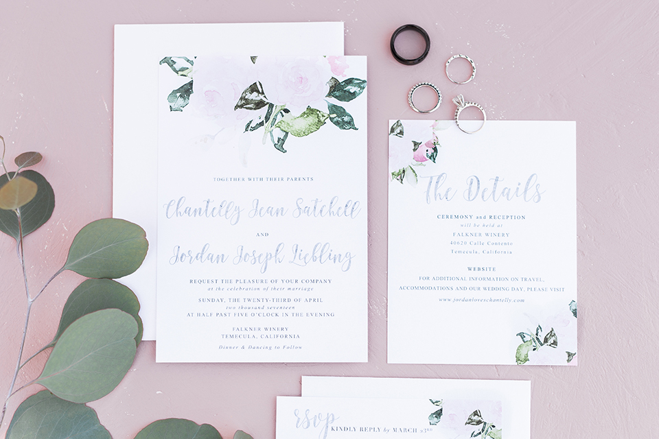 Temecula outdoor wedding at falkner winery wedding invitations white invitations with black calligraphy writing and greenery floral decor with wedding rings and light pink background wedding photo idea for invitations