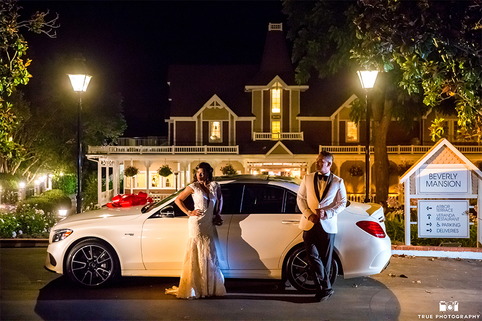 San diego outdoor wedding at the grand tradition bride ball gown with thin straps and crystal beading and lace detail with crystal belt and plunging neckline with groom white tuxedo jacket with black shawl lapel and black tuxedo pants with white dress shirt and big black bow tie standing by car