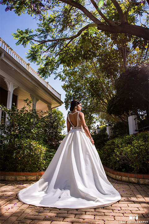 San diego outdoor wedding at the grand tradition bride ball gown with thin straps and crystal beading and lace detail with crystal belt and plunging neckline back of dress holding white floral bridal bouquet