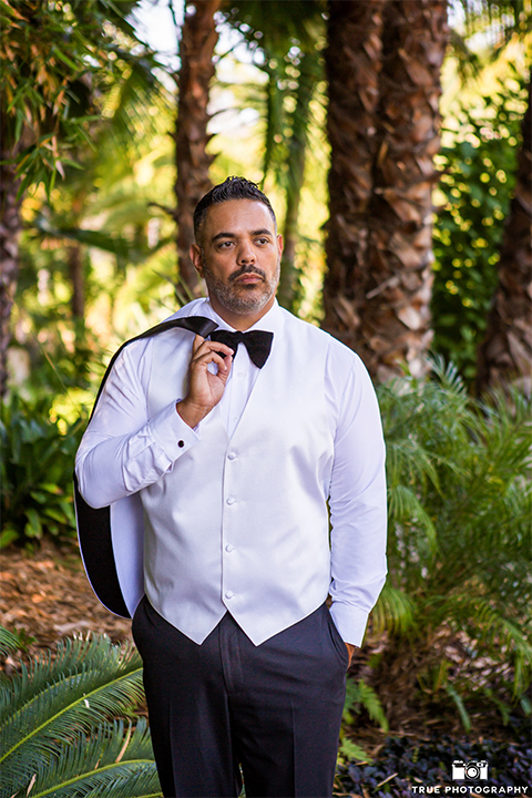 San diego outdoor wedding at the grand tradition groom white tuxedo jacket with black shawl lapel and white dress shirt with white vest and big black bow tie and black tuxedo pants holding jacket