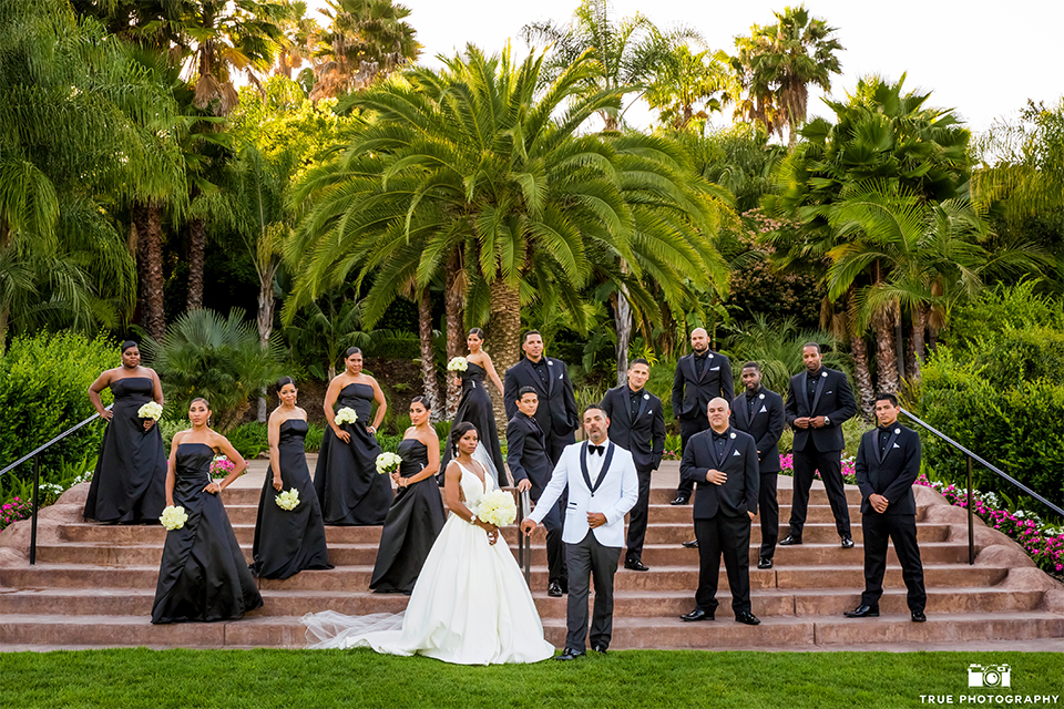 San diego outdoor wedding at the grand tradition bride ball gown with thin straps and crystal beading and lace detail with crystal belt and plunging neckline with groom white tuxedo jacket with black shawl lapel and black tuxedo pants with white dress shirt and big black bow tie with wedding party bridesmaids long black dresses and groomsmen black tuxedos with black shirts and black ties