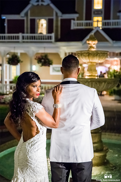 San diego outdoor wedding at the grand tradition bride ball gown with thin straps and crystal beading and lace detail with crystal belt and plunging neckline with groom white tuxedo jacket with black shawl lapel and black tuxedo pants with white dress shirt and big black bow tie hugging