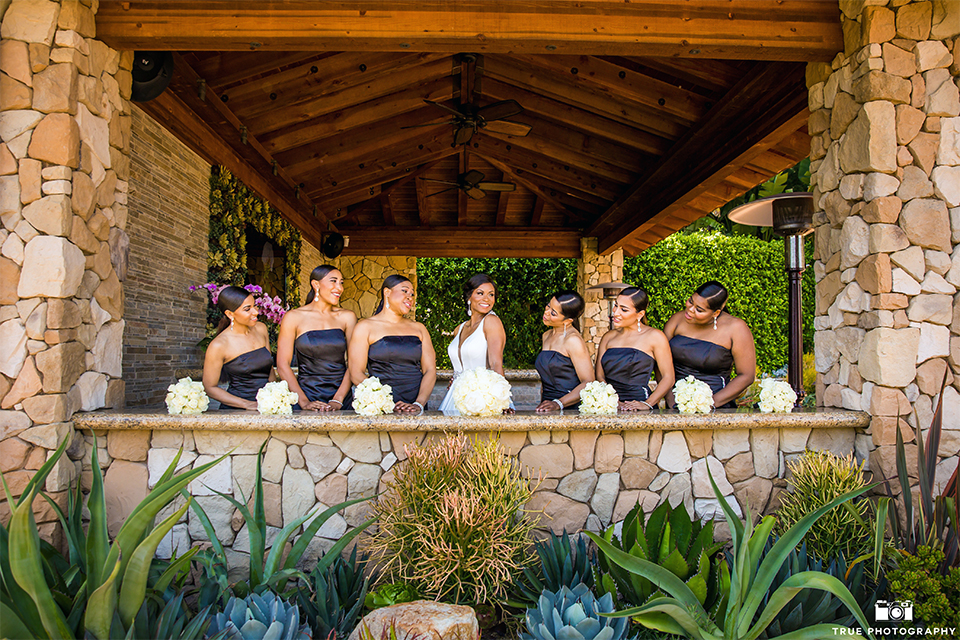 San diego outdoor wedding at the grand tradition bride ball gown with thin straps and crystal beading and lace detail with crystal belt and plunging neckline back of dress holding white floral bridal bouquet with bridesmaids long black dresses with white floral bouquets