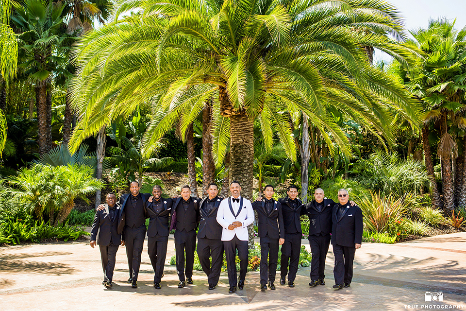 San diego outdoor wedding at the grand tradition groom white tuxedo jacket with black shawl lapel and white dress shirt with white vest and big black bow tie and black tuxedo pants with groomsmen black tuxedos with black shirts and black ties walking