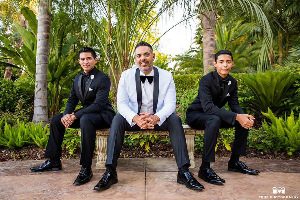 San diego outdoor wedding at the grand tradition groom white tuxedo jacket with black shawl lapel and white dress shirt with white vest and big black bow tie and black tuxedo pants with groomsmen black tuxedos with black shirts and black ties sitting