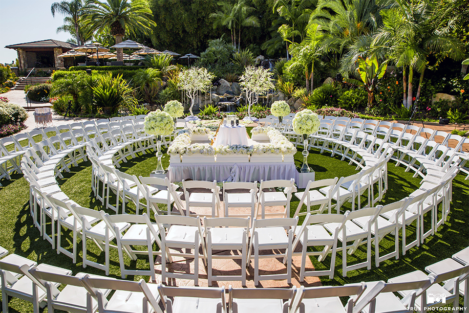San diego outdoor wedding at the grand tradition ceremony set up with white chairs in a circle formation and white altar with flower decor on the green grass wedding photo idea for ceremony