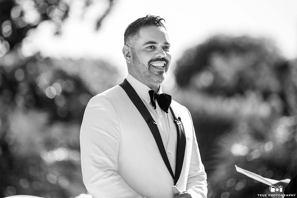 San diego outdoor wedding at the grand tradition groom white tuxedo jacket with black shawl lapel and white dress shirt with white vest and big black bow tie and black tuxedo pants watching bride walk down the aisle smiling black and white photo