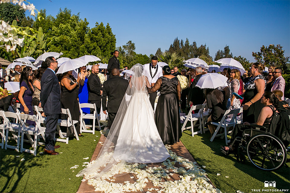 San diego outdoor wedding at the grand tradition bride ball gown with thin straps and crystal beading and lace detail with crystal belt and plunging neckline back of dress holding white floral bridal bouquet walking down the aisle with parents