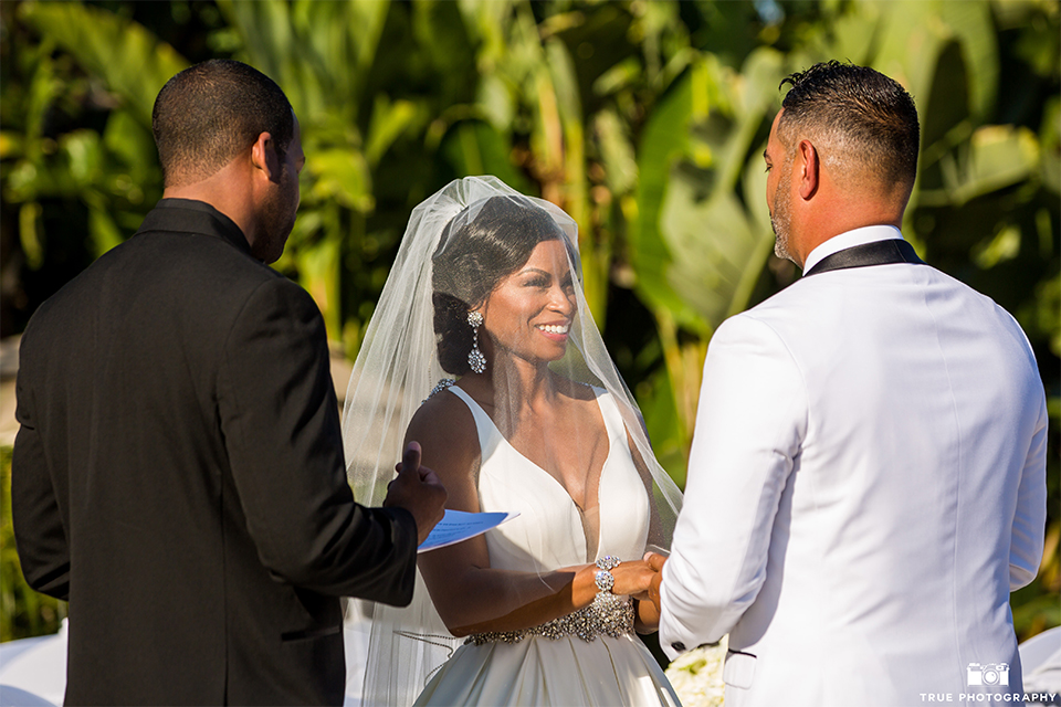 San diego outdoor wedding at the grand tradition bride ball gown with thin straps and crystal beading and lace detail with crystal belt and plunging neckline with groom white tuxedo jacket with black shawl lapel and black tuxedo pants with white dress shirt and big black bow tie holding hands during ceremony