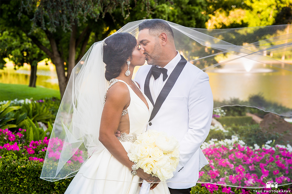 San diego outdoor wedding at the grand tradition bride ball gown with thin straps and crystal beading and lace detail with crystal belt and plunging neckline with groom white tuxedo jacket with black shawl lapel and black tuxedo pants with white dress shirt and big black bow tie kissing under veil bride holding white floral bridal bouquet