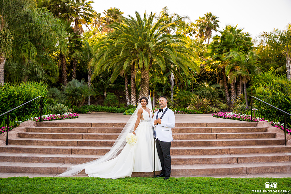 San diego outdoor wedding at the grand tradition bride ball gown with thin straps and crystal beading and lace detail with crystal belt and plunging neckline with groom white tuxedo jacket with black shawl lapel and black tuxedo pants with white dress shirt and big black bow tie hugging and bride holding white floral bridal bouquet