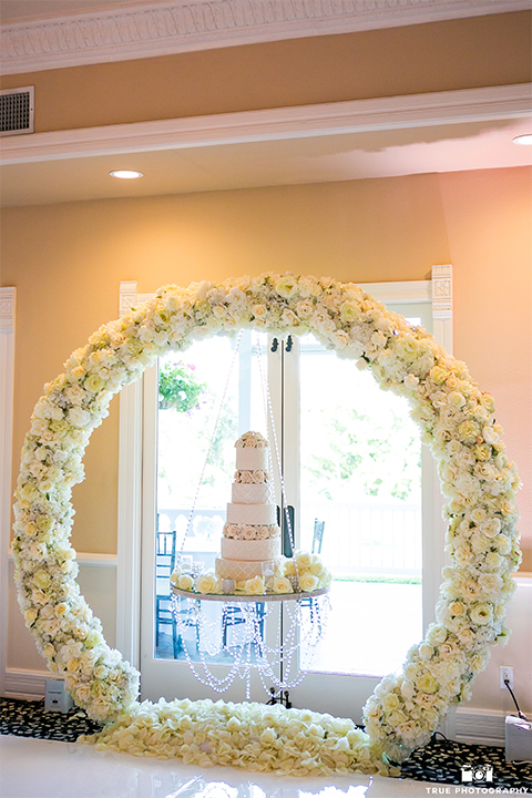 San diego outdoor wedding at the grand tradition reception table set up with white table linen and grey chairs with white linen decor and all white flower centerpieces with white place settings and glassware with white flowers in circle with four tier white wedding cake