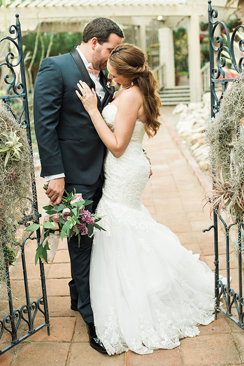 Orange county outdoor wedding at sherman library and gardens bride form fitting strapless lace gown with sweetheart neckline and pearl necklace with groom navy blue shawl lapel tuxedo with matching vest and white dress shirt with blush pink bow tie and white floral boutonniere hugging