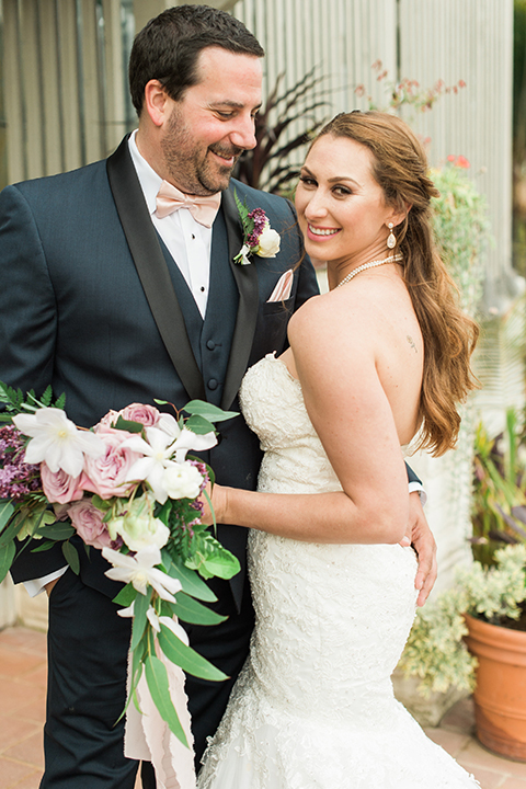 Orange county outdoor wedding at sherman library and gardens bride form fitting strapless lace gown with sweetheart neckline and pearl necklace with groom navy blue shawl lapel tuxedo with matching vest and white dress shirt with blush pink bow tie and white floral boutonniere hugging and groom holding white and pink floral bridal bouquet