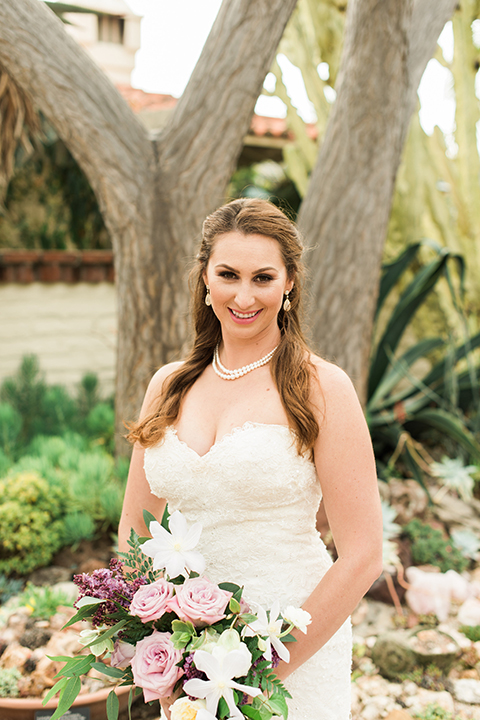 Orange county outdoor wedding at sherman library and gardens bride form fitting strapless lace gown with sweetheart neckline and pearl necklace holding white and pink floral bridal bouquet