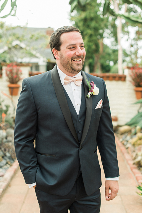 Orange county outdoor wedding shoot at sherman library and gardens groom navy blue shawl lapel tuxedo with matching vest and white dress shirt with blush pink bow tie and pocket square with white floral boutonniere