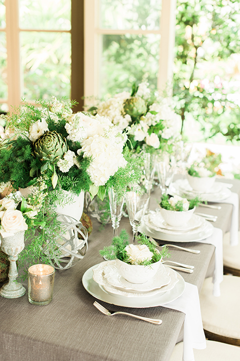 Orange county outdoor wedding shoot at sherman library and gardens table set up with light grey table linen and white place settings with green and white flower centerpiece decor with gold silverware and light brown and white wood chairs