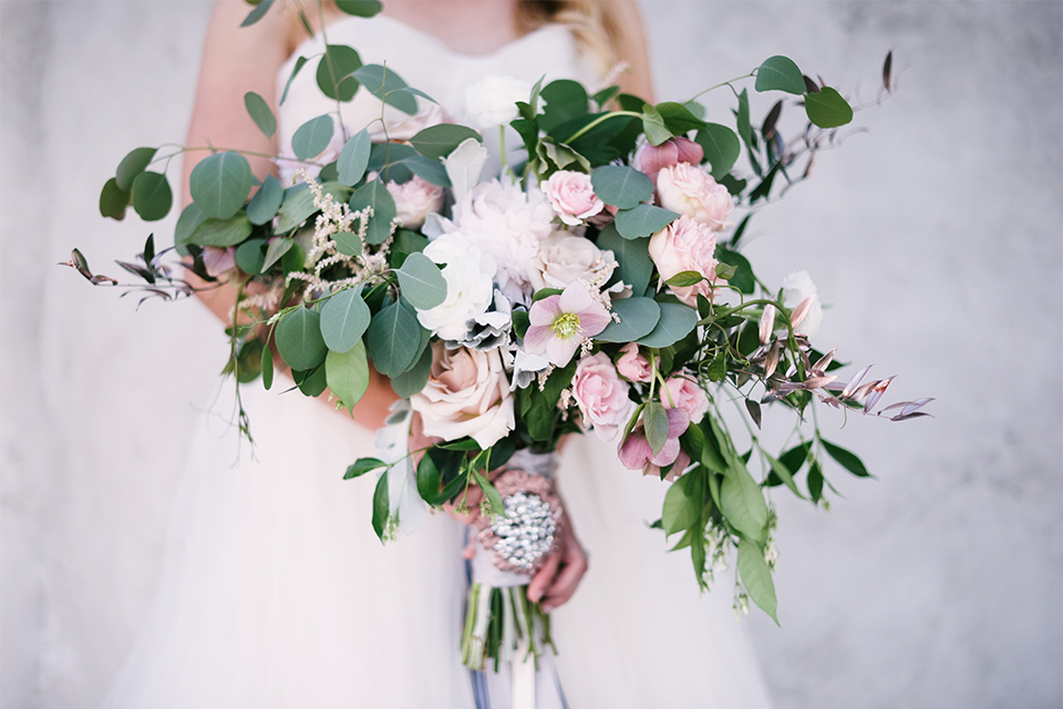 Orange county outdoor wedding at old ranch country club bride strapless ballgown with a sweetheart neckline and beaded detail holding light pink and green floral bridal bouquet close up