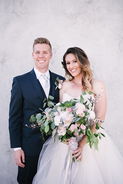 Orange county outdoor wedding at old ranch country club bride strapless ballgown with a sweetheart neckline and beaded detail with groom navy notch lapel suit with matching vest and white dress shirt with long silver tie and white floral boutonniere hugging