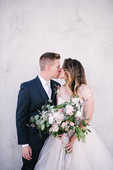 Orange county outdoor wedding at old ranch country club bride strapless ballgown with a sweetheart neckline and beaded detail with groom navy notch lapel suit with matching vest and white dress shirt with long silver tie and white floral boutonniere kissing and bride holding light pink and green floral bridal bouquet