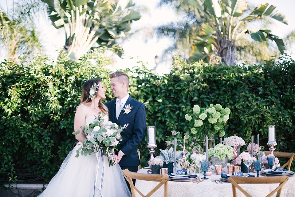 Orange county outdoor wedding at old ranch country club bride strapless ballgown with a sweetheart neckline and beaded detail with groom navy notch lapel suit with matching vest and white dress shirt with long silver tie and white floral boutonniere standing by table bride holding light pink and green floral bridal bouquet