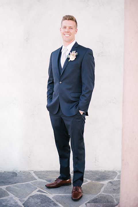 Orange county outdoor wedding shoot at old ranch country club groom navy blue notch lapel suit with matching vest and white dress shirt with long silver tie and white floral boutonniere standing with hands in pockets