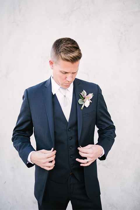 Orange county outdoor wedding shoot at old ranch country club groom navy blue notch lapel suit with matching vest and white dress shirt with long silver tie and white floral boutonniere standing and holding jacket